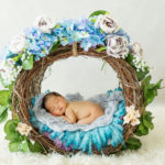 baby girl in basket with blue flowers