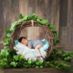 Baby boy in garland basket.